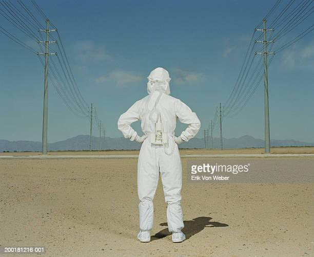 Man wearing protective suit in desert, rear view