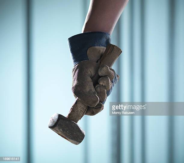 Man wearing protective work glove holding hammer