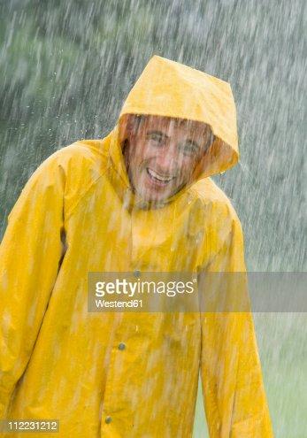 Man wearing rain coat standing in rain, portrait