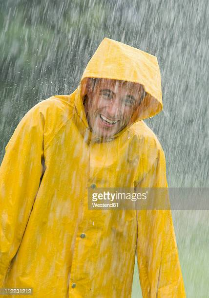 Man wearing rain coat standing in rain, portrait