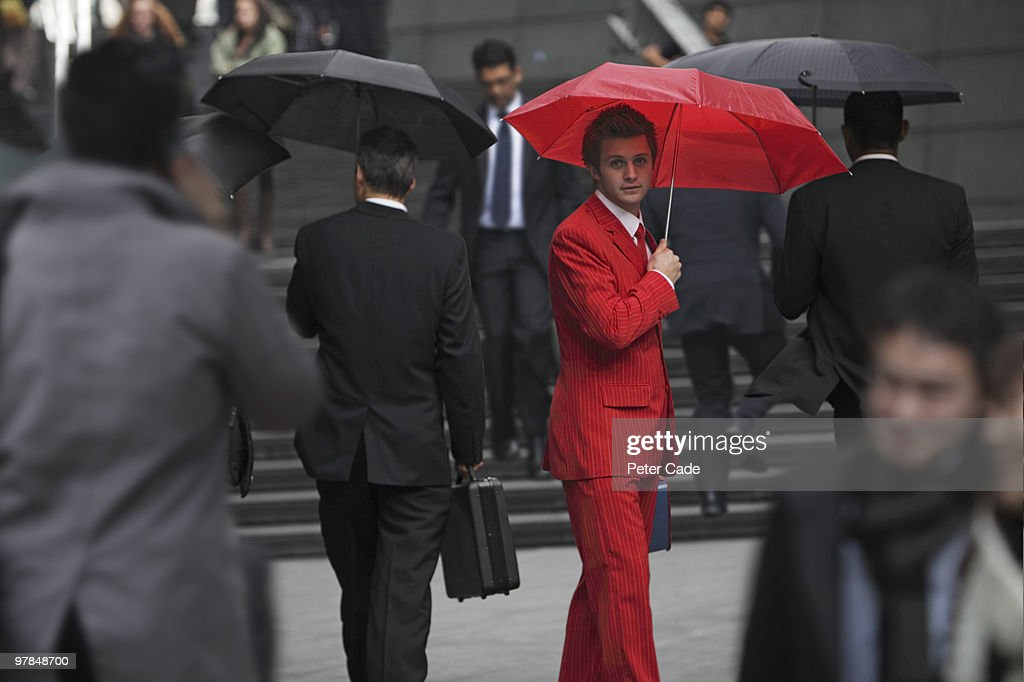 Man wearing red suit, holding umbrella in city : Stock Photo