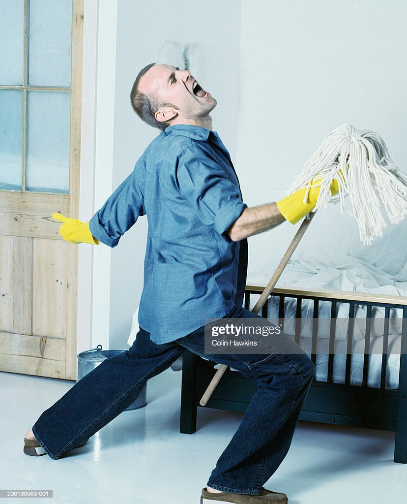 Man wearing rubber gloves singing, using mop as 'microphone stand'