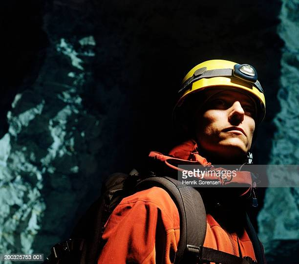 Man wearing safety helmet and torch in cave