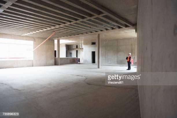 Man wearing safety vest looking around in building under construction