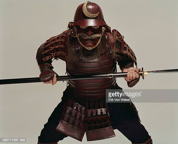 Man wearing samurai costume and holding sword in fighting position