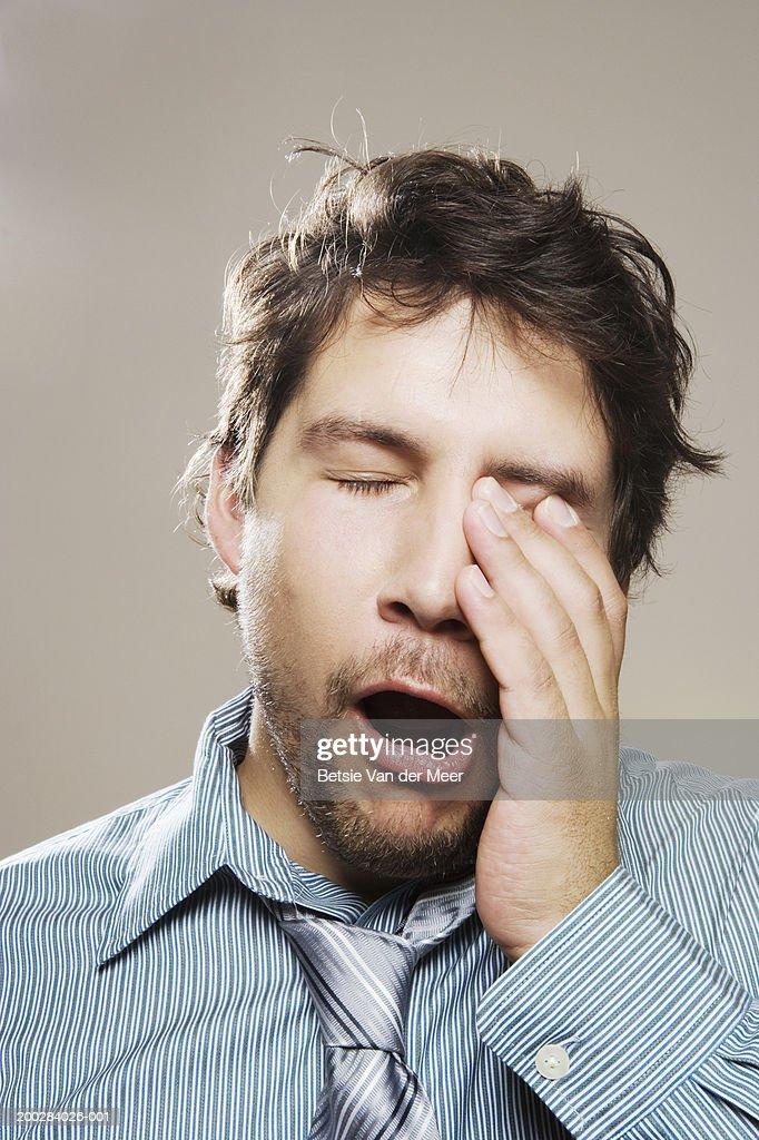 Man wearing shirt and loosened tie yawning, rubbing eye, close-up