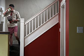 Man wearing shirt and tie and boxer shorts descending stairs drinking coffee at home