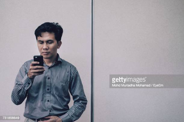 Man Wearing Shirt Using Phone While Standing Against Wall