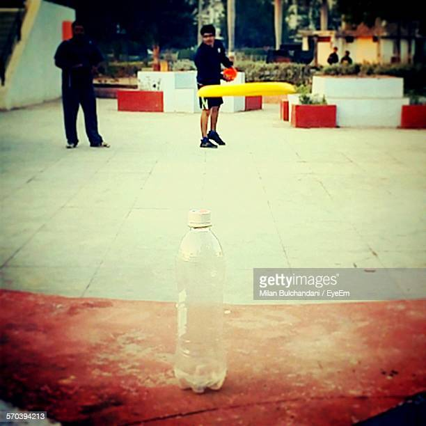 Man Wearing Shorts Aiming Bottle By Frisbee Outdoors
