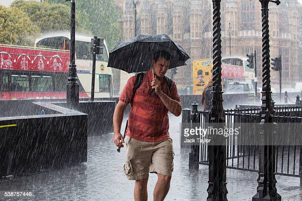A man wearing shorts and holding an umbrella walks through heavy rain in Westminster on June 8 2016 in London England The Met Office has issued flood...