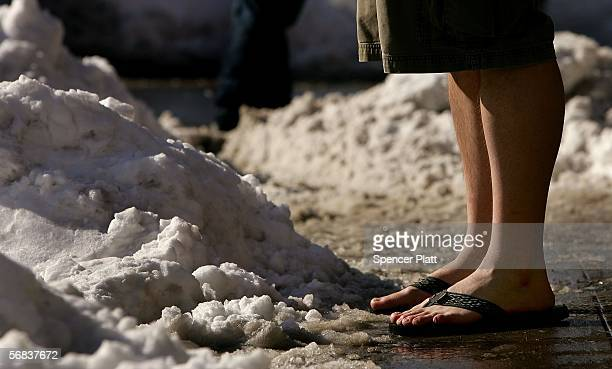 A man wearing shorts and sandles stands on a snowy sidewalk the morning after a Northeast storm dropped more than twofeet of snow February 13 2006 in...