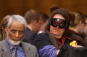 A man wearing ski goggles and a teddy bear hat attends a Senate Foreign Relations Committee hearing with Secretary of State John Kerry about a...