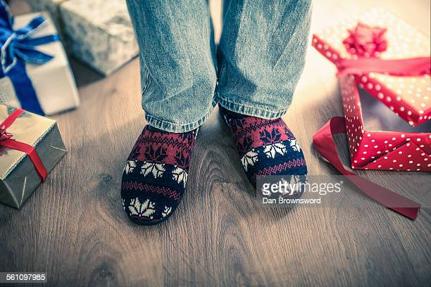 Man wearing slippers with christmas gifts on floor