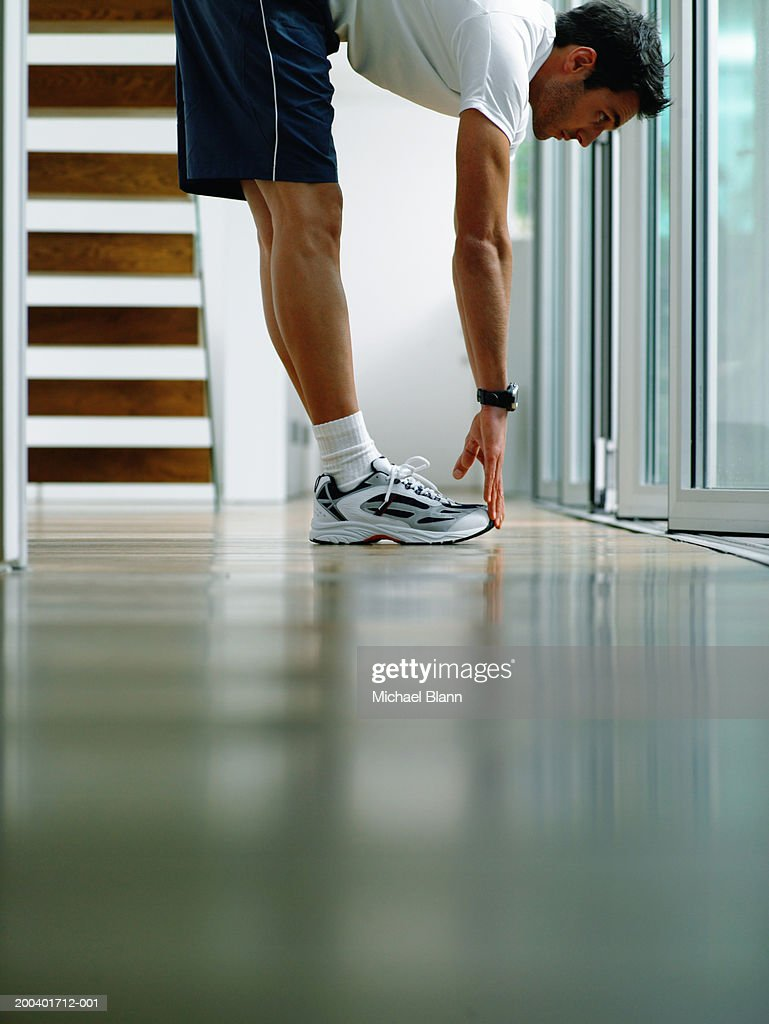 Man wearing sports clothes performing stretch in hallway, ground view