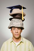 Man wearing stack of various hats
