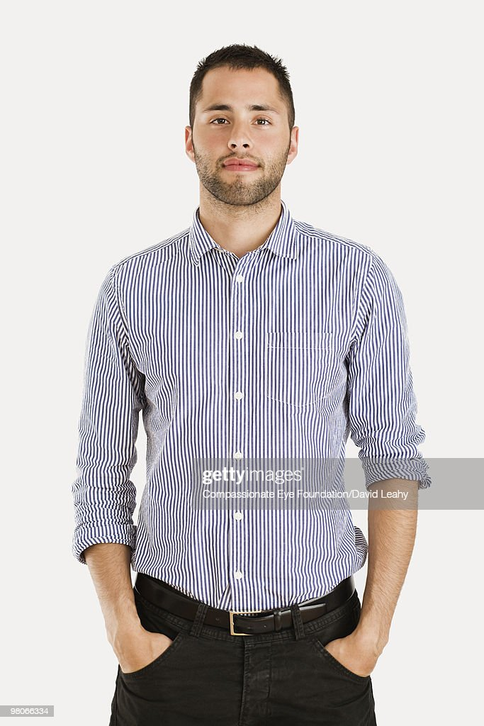 Man wearing striped shirt with hands in pockets : Stock Photo