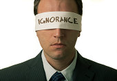 Man wearing suit and tie and blindfold with ignorance on it