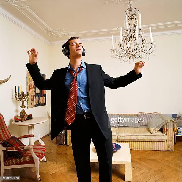 Man Wearing Suit Dancing with Headphones in Living Room