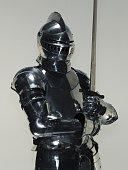 Man wearing suit of armor and holding sword