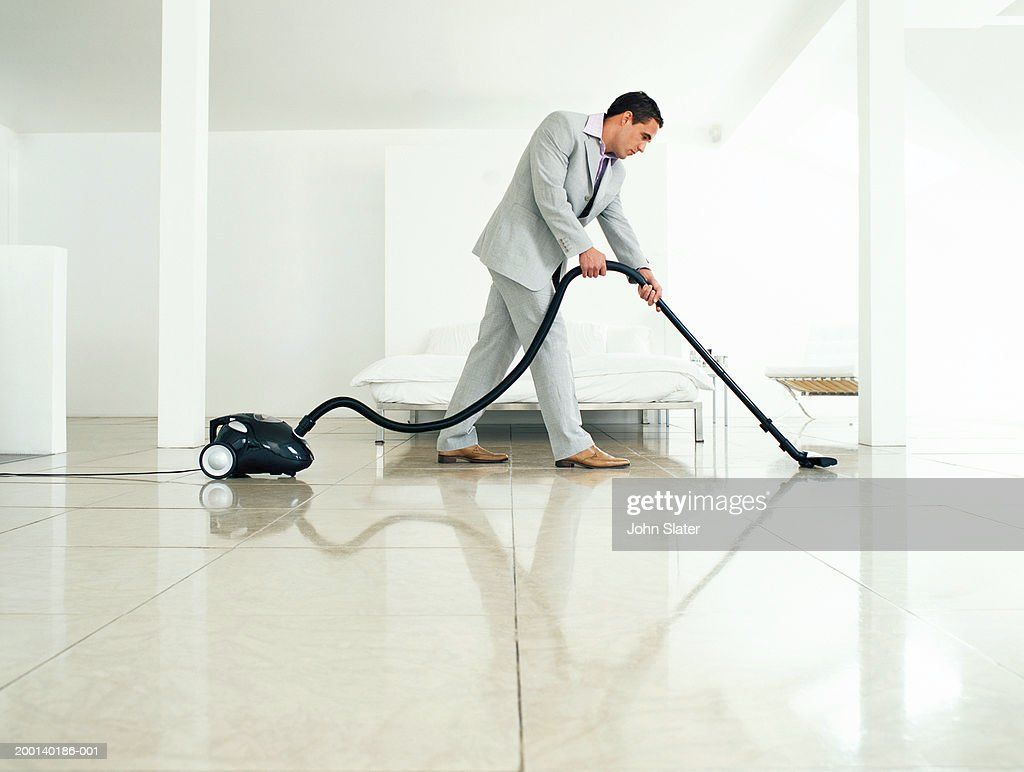 Man wearing suit vacuuming floor, side view : Stock Photo