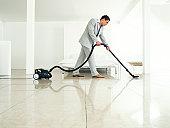 Man wearing suit vacuuming floor, side view