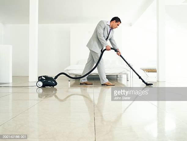 Man wearing suit vacuuming floor, side view