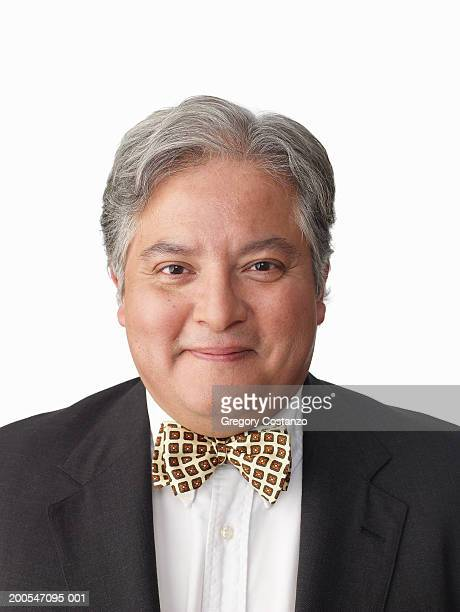 Man wearing suit with bow tie, on white background, portrait