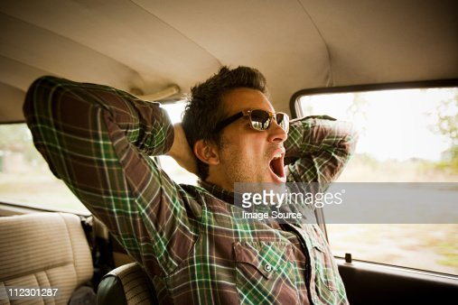 Man wearing sunglasses and yawning in car