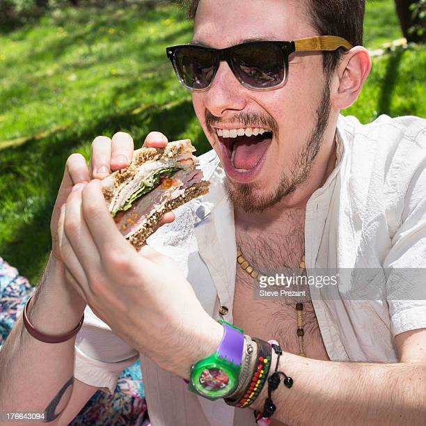 Man wearing sunglasses eating sandwich