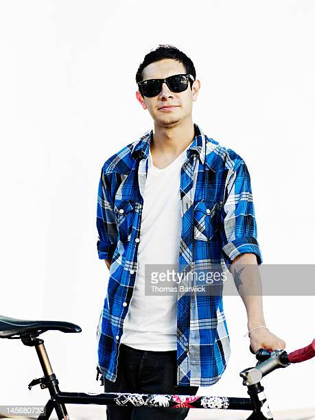 Man wearing sunglasses holding bicycle