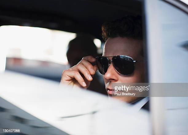 Man wearing sunglasses in backseat of car