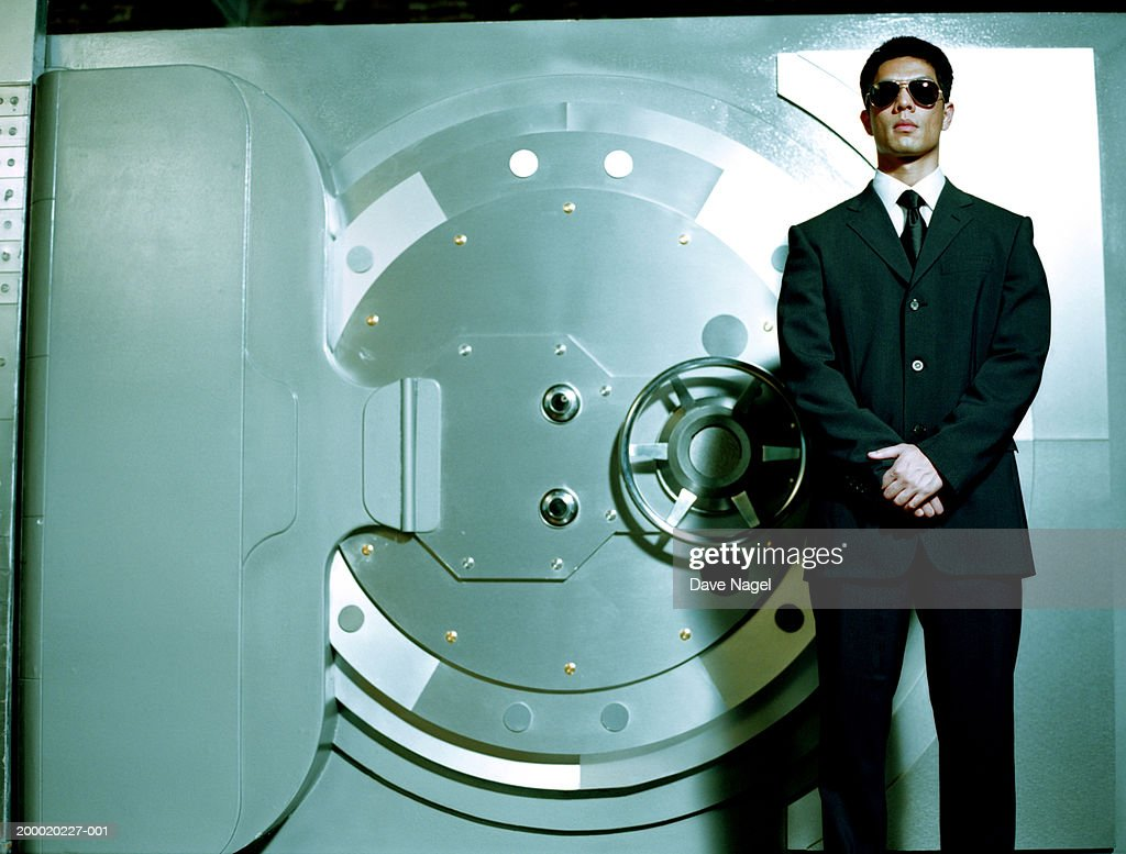 Man wearing sunglasses in front of vault
