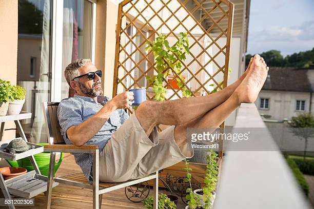Man wearing sunglasses relaxing on his balcony with a cup of coffee