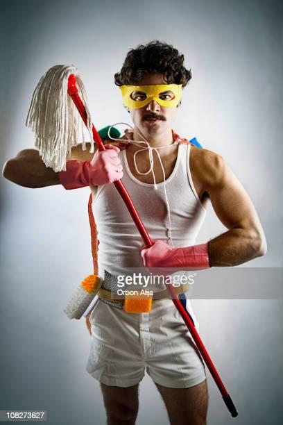 Mann mit Superhelden-Maske und Reinigungsmaterial hält,-Mop