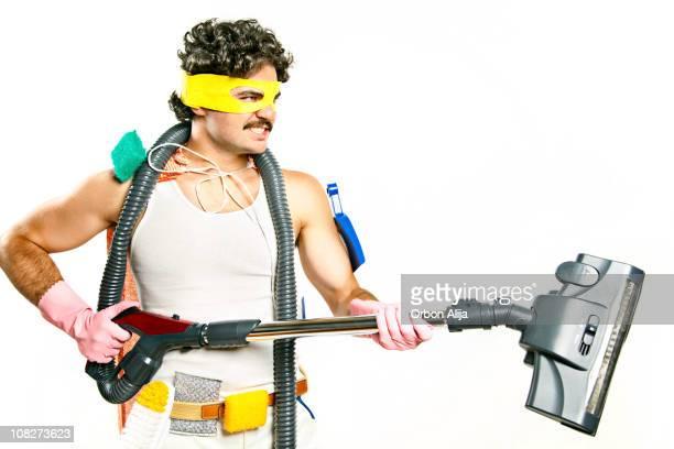Mann mit Superhelden-Maske, die Vakuum und Reinigungsmaterial
