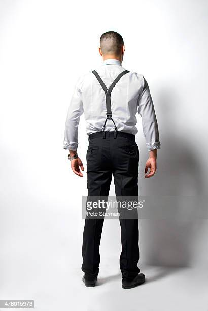 Man wearing suspenders facing wall.