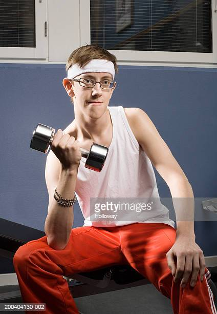 Man wearing sweatband and spectacles lifting dumbbell in gym, smiling