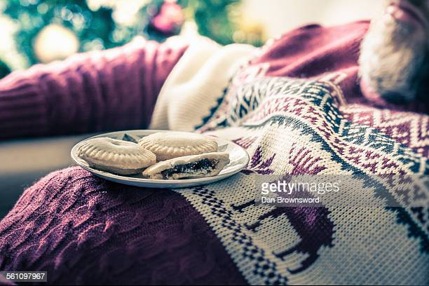 Man wearing sweater asleep with mince pies on chest