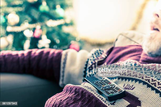 Man wearing sweater asleep with remote control on chest