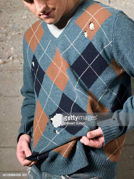 Man wearing sweater with holes, outdoors