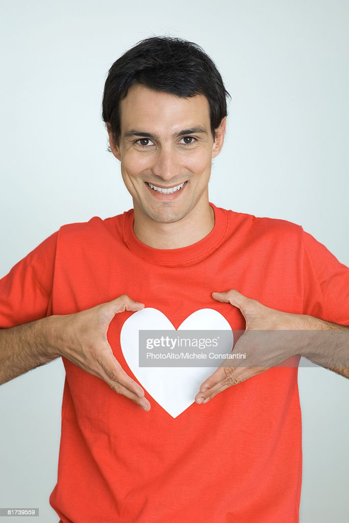 Man wearing tee-shirt with heart symbol, holding hands around heart, smiling at camera