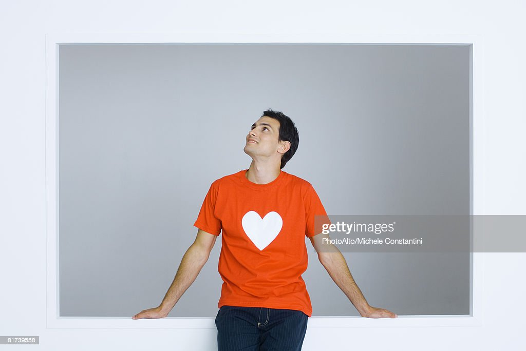 Man wearing tee-shirt with heart symbol, looking up, smiling