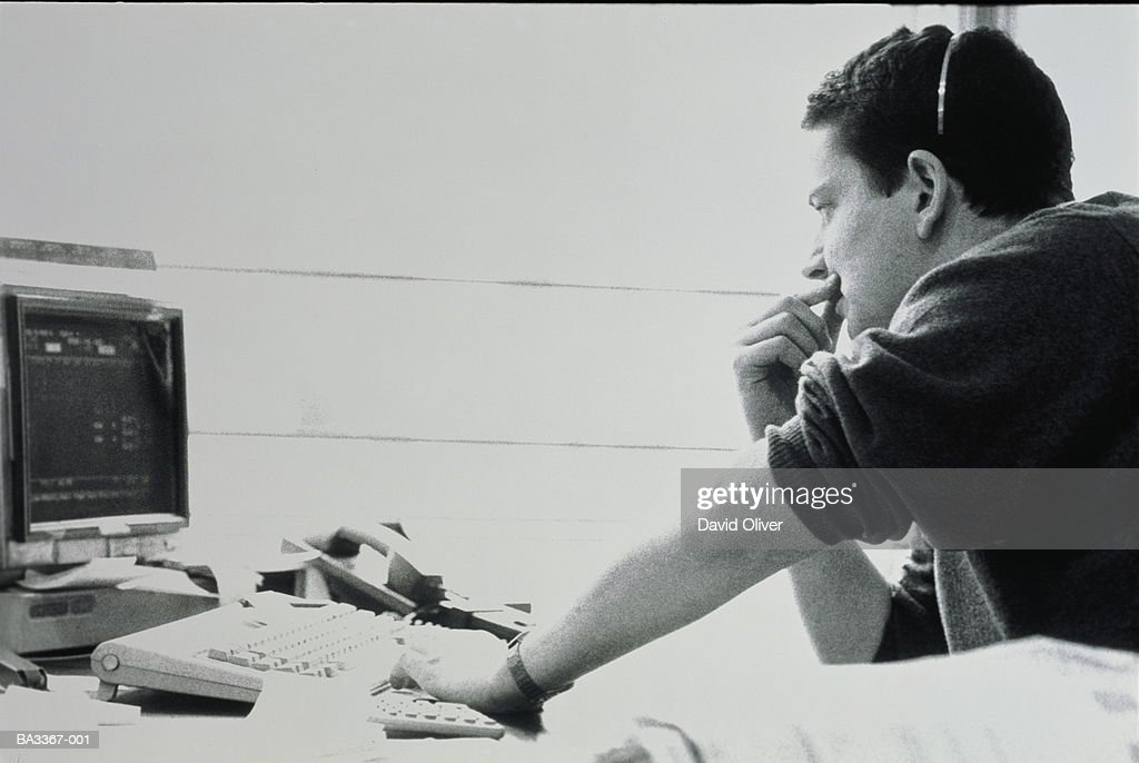 Man wearing telephone headset, sitting at computer terminal (b&w) : Stock Photo