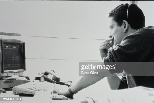 Man wearing telephone headset, sitting at computer terminal (b&w) : ストックフォト