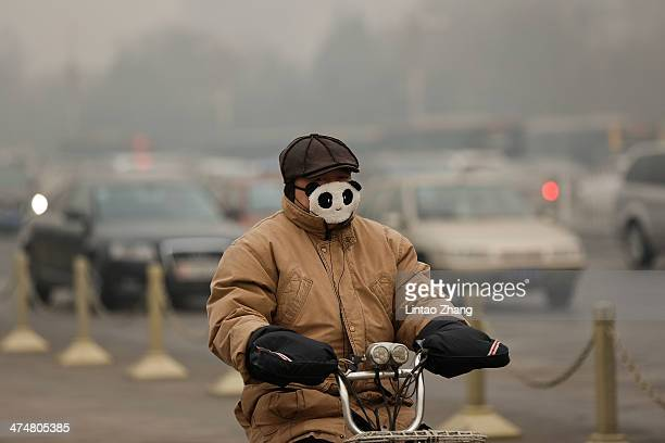 A man wearing the mask rides a bicycle during severe pollution on February 25 2014 in Beijing China The air pollution has caused an increase in the...