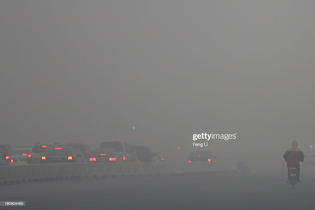 A man wearing the mask rides amid fog during severe pollution on January 29, 2013 in Beijing, China. The 4th dense fog envelops Beijing with pollution at hazardous levels in January.