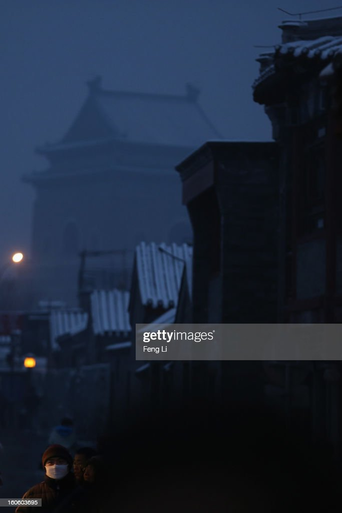 A man wearing the mask walks through an alley near the Bell Tower during severe pollution on February 3, 2013 in Beijing, China. Houhai Lake is a popular place for winter sport and entertainment in Beijing.