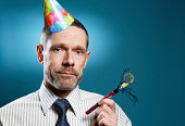 Man Wearing Tie With Party Hat And Horn Blower