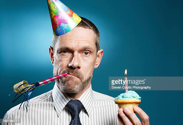Man Wearing Tie With Party Hat Horn Blower And Cup