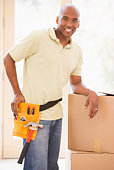 Man wearing tool belt standing by boxes in new home smiling